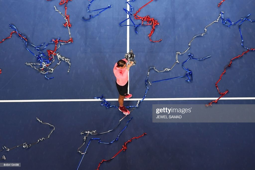 Spain's Rafael Nadal poses with his winning trophy after defeating South Africa's Kevin Anderson during their 2017 US Open Men's Singles final match at the USTA Billie Jean King National Tennis Center in New York on September 10, 2017. Rafael Nadal raced to a third US Open title and 16th Grand Slam crown on Sunday with a 6-3, 6-3, 6-4 rout of South African giant Kevin Anderson. / AFP PHOTO / Jewel SAMAD