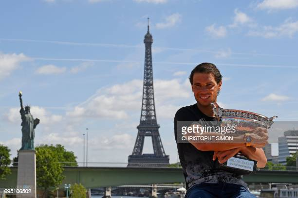 Spain's Rafael Nadal poses with the winner's trophy a day after he won the men's Roland Garros 2017 French Open on June 12 2017 in Paris with the...