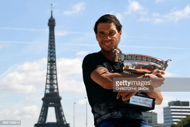 TOPSHOT Spain's Rafael Nadal poses with the winner's trophy a day after he won the men's Roland Garros 2017 French Open on June 12 2017 in Paris with...