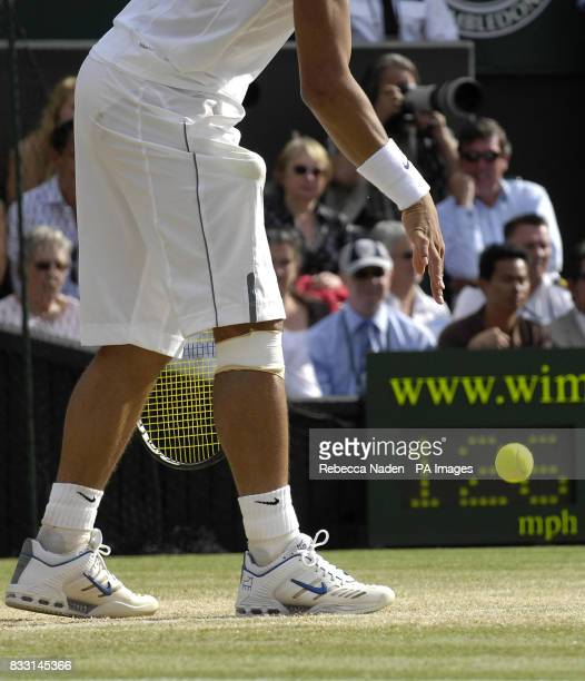 Spain's Rafael Nadal prepares to serve following treatment on his knee during his match with Switzerland's Roger Federer during The All England Lawn...