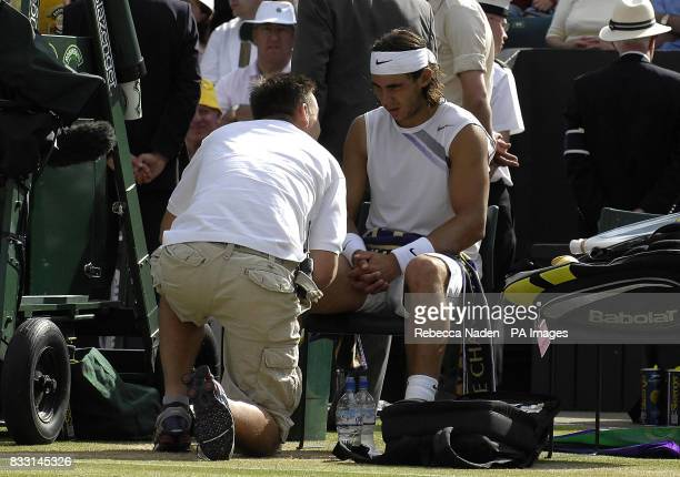 Spain's Rafael Nadal receives medical treatment during his match with Switzerland's Roger Federer during The All England Lawn Tennis Championship at...
