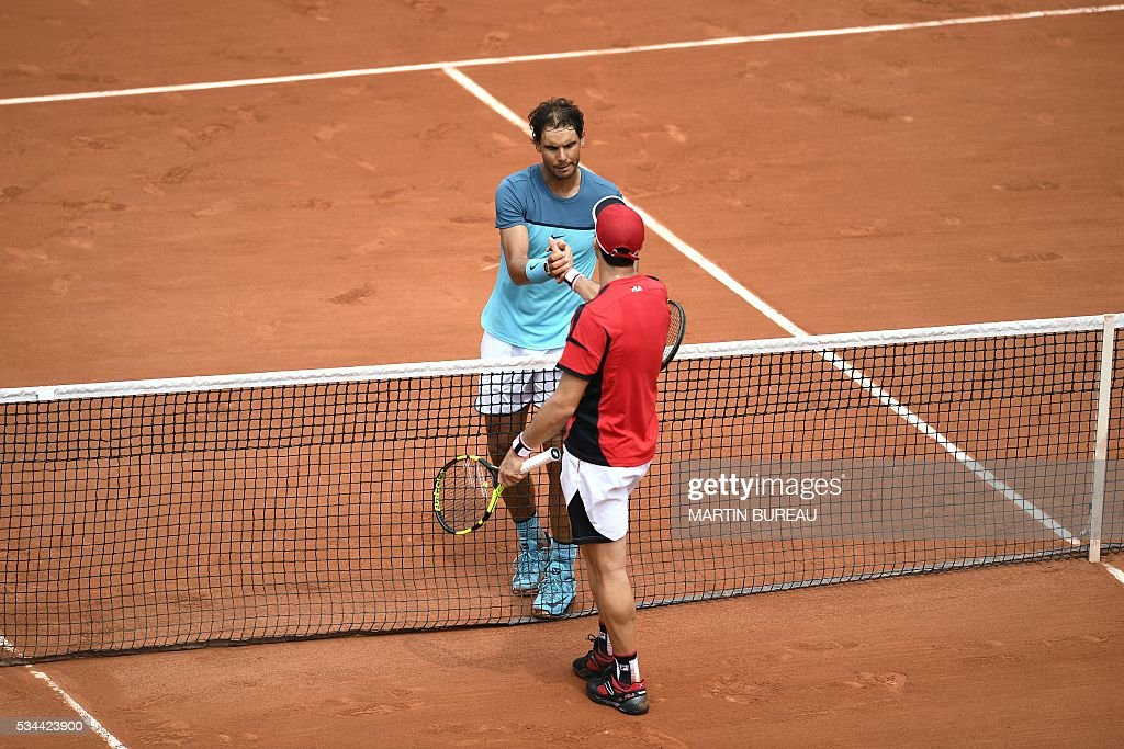 Spain's Rafael Nadal (back) shakes hands with Argentina's Facundo Bagnis after winning their men's second round match at the Roland Garros 2016 French Tennis Open in Paris on May 26, 2016. / AFP / MARTIN