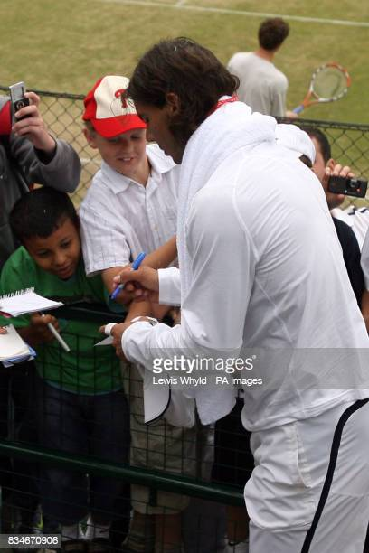 Spain's Rafael Nadal signs autographs for fans during the Wimbledon Championships 2008 at the All England Tennis Club in Wimbledon