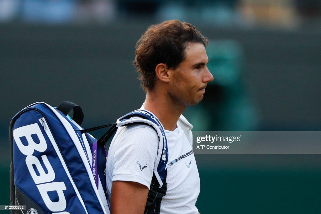 TOPSHOT - Spain's Rafael Nadal waits for Luxembourg's Gilles Muller to collect his bag so that they can leave the court together after Muller won their men's singles fourth round match on the seventh day of the 2017 Wimbledon Championships at The All England Lawn Tennis Club in Wimbledon, southwest London, on July 10, 2017. Muller won 6-3, 6-4, 3-6, 4-6, 15-13. / AFP PHOTO / Adrian DENNIS / RESTRICTED