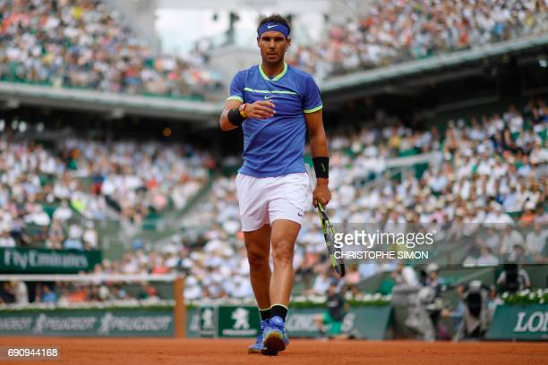 TOPSHOT Spain's Rafael Nadal walks on the court during his tennis match against Netherlands' Robin Haase at the Roland Garros 2017 French Open on May...