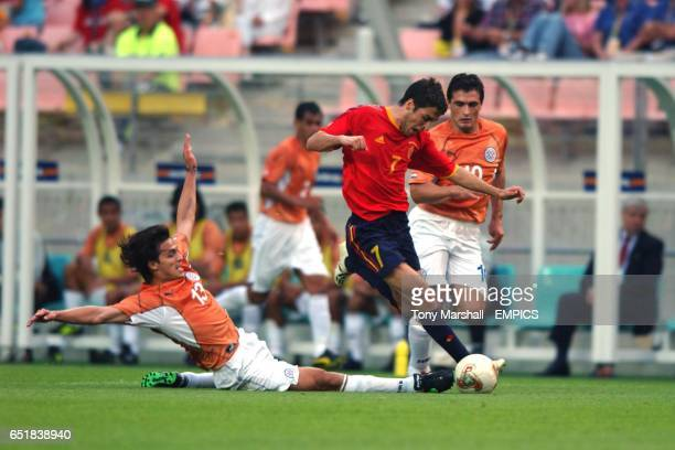 Spain's Raul is tackled by Paraguay's Carlos Paredes