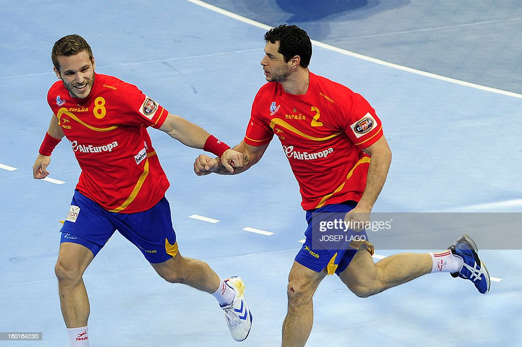 Spain's right wing Victor Tomas (L) celebrates a goal with Spain's left back Alberto Entrerrios during the 23rd Men's Handball World Championships final match Spain vs Denmark at the Palau Sant Jordi in Barcelona on January 27, 2013. AFP PHOTO/ JOSEP LAGO