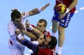 Spain's right wing Victor Tomas vies with Serbia's left back Milos Dragas and Serbia's pivot Alem Toskic during the 23rd Men's Handball World...