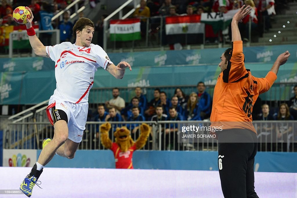 Spain's rightback Angel Montoro (L) shoots past Egypt's goalkeeper Hady Mohamed (R) during the 23rd Men's Handball World Championships preliminary round Group D match Egypt vs Spain at the Caja Magica in Madrid on January 14, 2013.