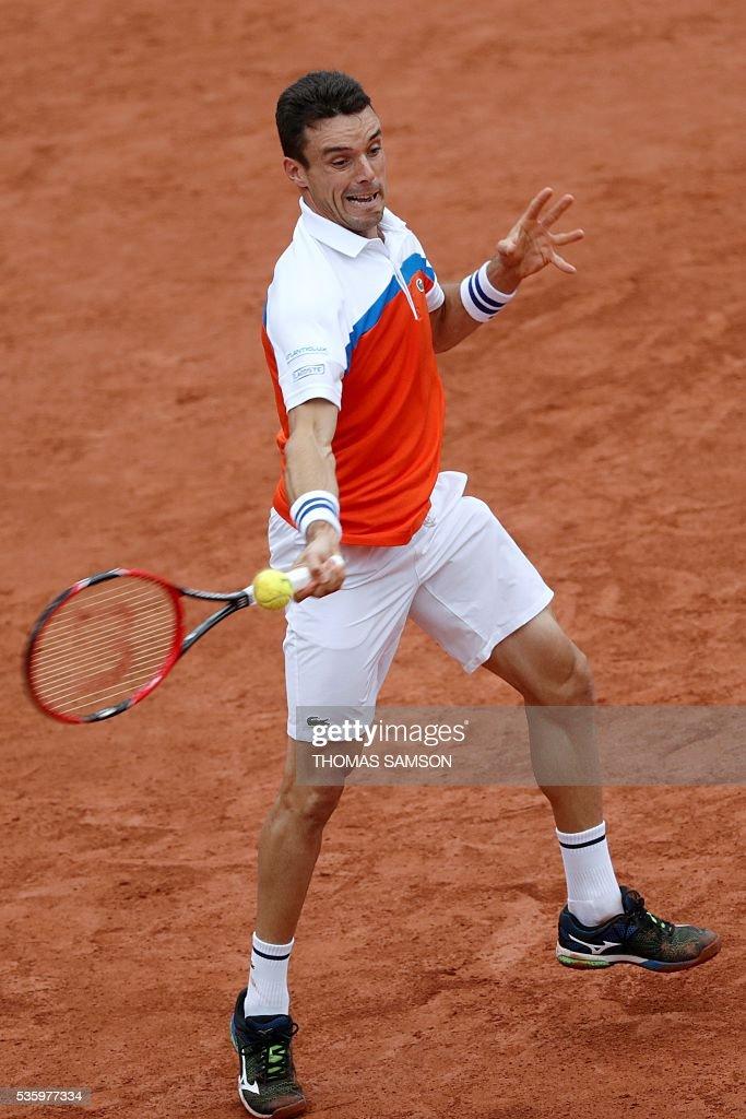 Spain's Roberto Bautista-Agut returns the ball to Serbia's Novak Djokovic during their men's fourth round match at the Roland Garros 2016 French Tennis Open in Paris on May 31, 2016. / AFP / Thomas SAMSON