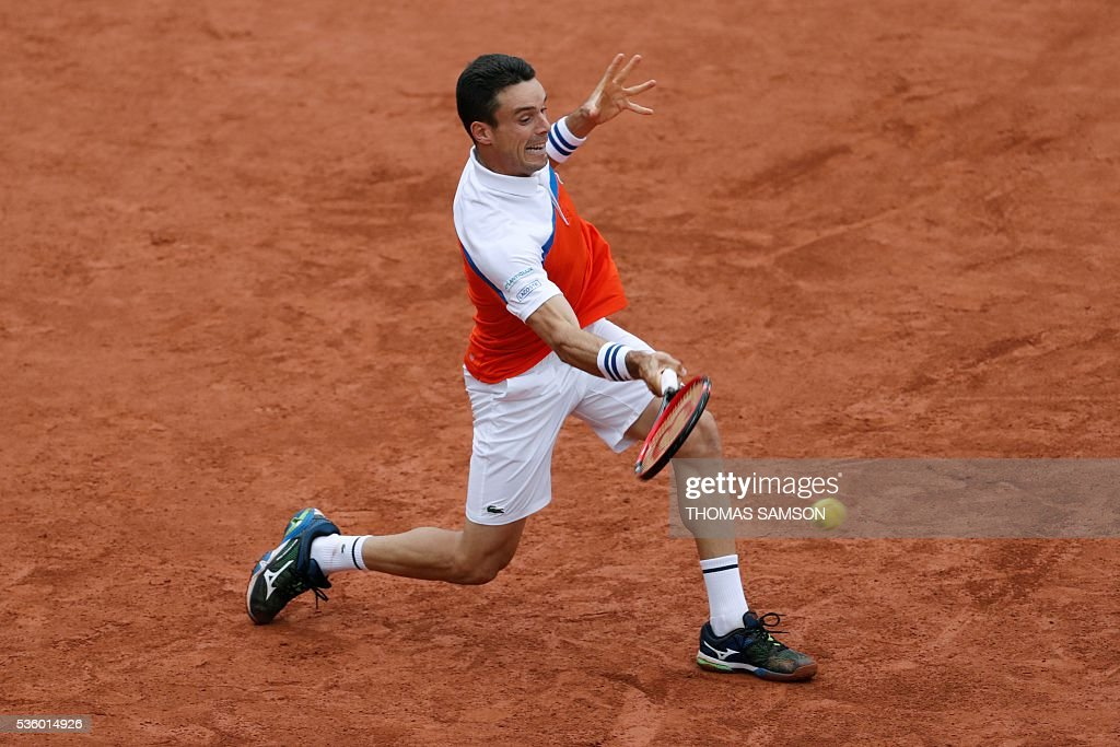Spain's Roberto Bautista-Agut returns the ball to Serbia's Novak Djokovic during their men's fourth round match at the Roland Garros 2016 French Tennis Open in Paris on May 31, 2016. / AFP / Thomas SAMSON