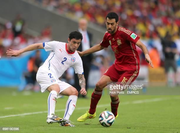 Spain's Sergio Busquets and Chile's Eugenio Mena battle for the ball
