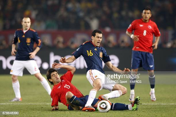 Spain's Sergio Busquets and Chile's Marco Estrada battle for the ball