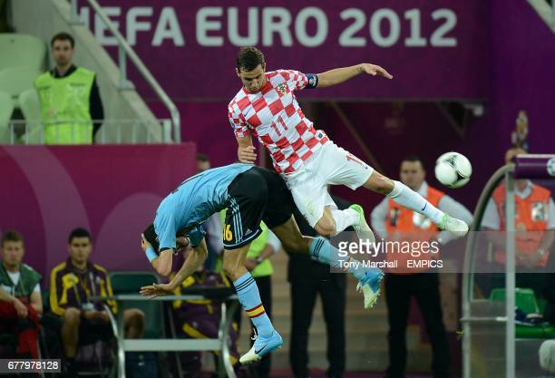 Spain's Sergio Busquets and Croatia's Darijo Srna battle for the ball in the air