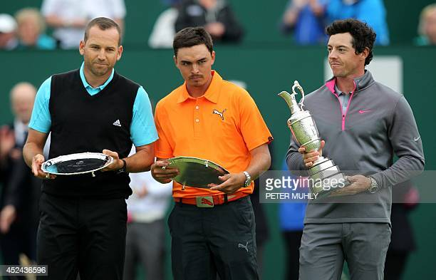 Spain's Sergio Garcia and US golfer Rickie Fowler stand with their second place trophies beside Northern Ireland's Rory McIlroy after finishing two...