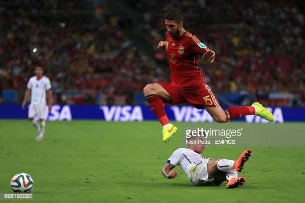 Spain's Sergio Ramos leaps a challenge from Chile's Eduardo Vargas