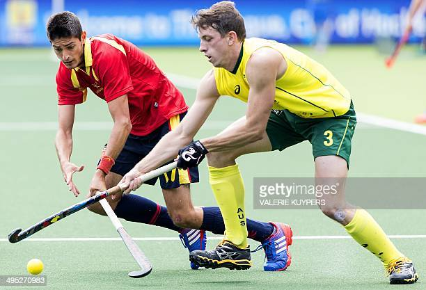 Spain's Xavier Lleonart vies with 's Simon Orchard during a group stage match in the men's tournament of the Field Hockey World Cup in The Hague The...