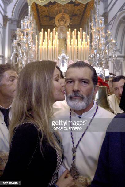 Spanish actor Antonio Banderas is kissed by his girlfriend Nicole Kimpel as he takes part in the 'Lagrimas y Favores' brotherhood procession on April...