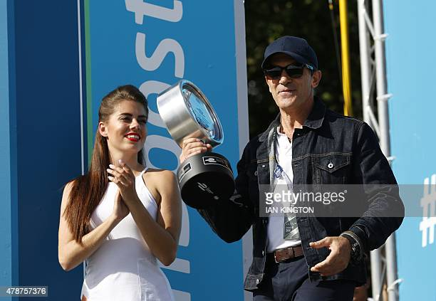 Spanish actor Antonio Banderas presents the second place trophy on the podium after the Round 10 race at 2015 FIA Formula E London ePrix championship...