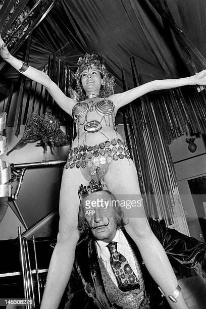 Spanish artist Salvador Dali celebrates the Epiphany day with a girl wearing a Jean Chenaf creation on February 3 1972 at his residence in the...