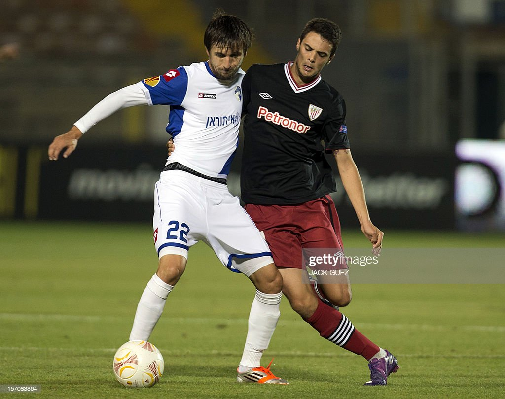 Spanish Athletic Club's Erik Moran (R) is challenged by Israeli Hapoel Kiryat Shmona's midfielder Darko Tasevski (L) during their UEFA Europa League Group I qualifying football match at the Kiryat Eliezer Stadium in the Mediterranean coastal city of Haifa on November 28, 2012.