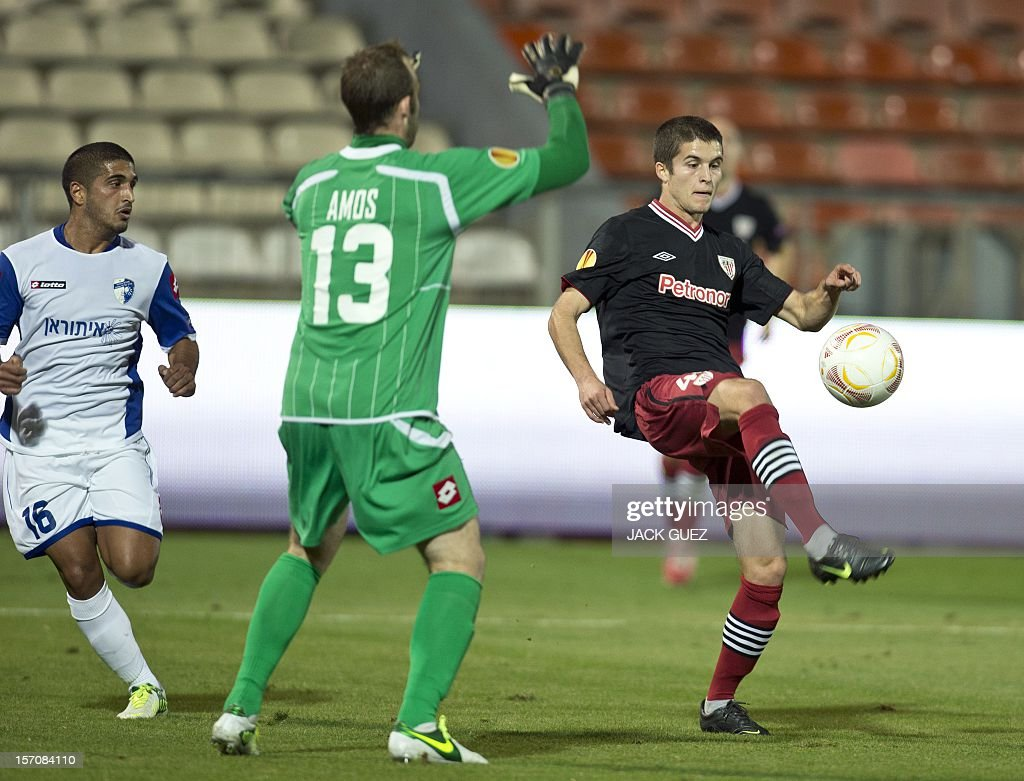 Spanish Athletic Clubs Jon Xabier Vidal (R) is challenged by Israeli Hapoel Kiryat Shmonas goalkeeper Daniel Amos (C) during their UEFA Europa League Group I qualifying football match at the Kiryat Eliezer Stadium, in the Mediterranean coastal city of Haifa, on November 28, 2012.