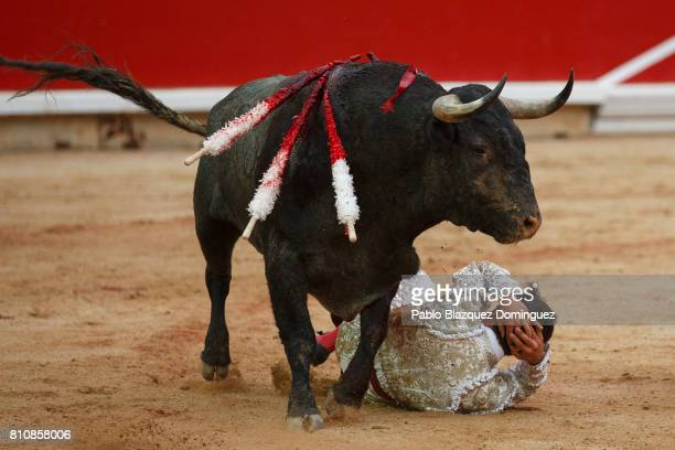 Spanish bullfighter Gonzalo Caballero rolls on the ground after being tossed by a bull from Jose Escolar Gil's fighting bulls during a bullfight on...