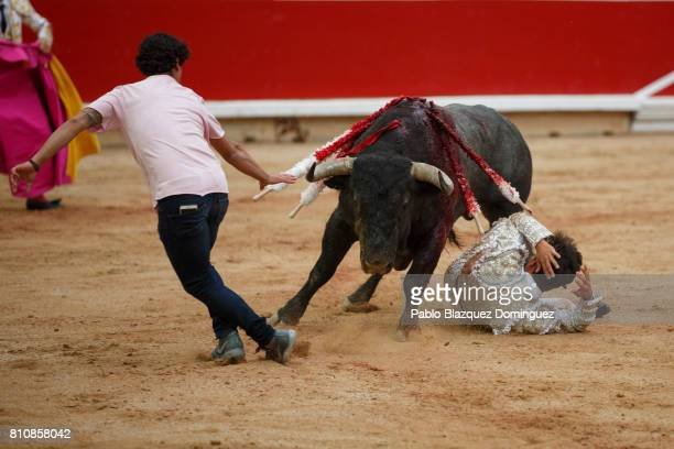 Spanish bullfighter Miguel Abellan steps in the bullring to help Spanish bullfighter Gonzalo Caballero as he rolls on the ground after being tossed...