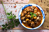high-angle shot of a ceramic bowl with spanish caracoles en salsa, cooked snails in sauce, on a rustic wooden table