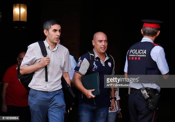 Spanish Civil Guard officers in plainclothes walk past a Mosso D'Esquadra as they leave after a search at the Generalitat in Barcelona on July 20...