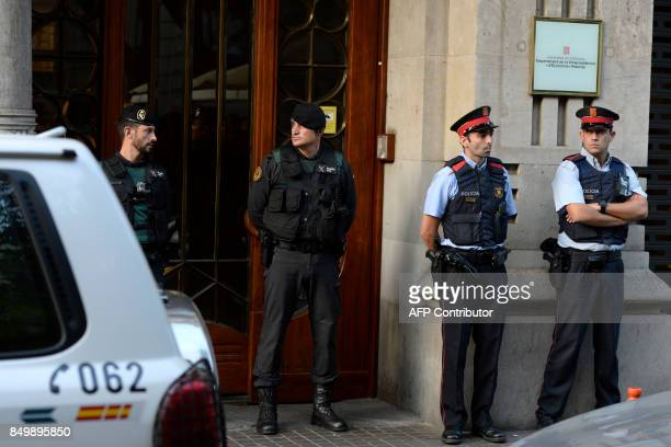 Spanish Civil Guards and Catalan regional police officers 'Mossos D'Esquadra' stand in front of the Economy headquarters of Catalonia's regional...