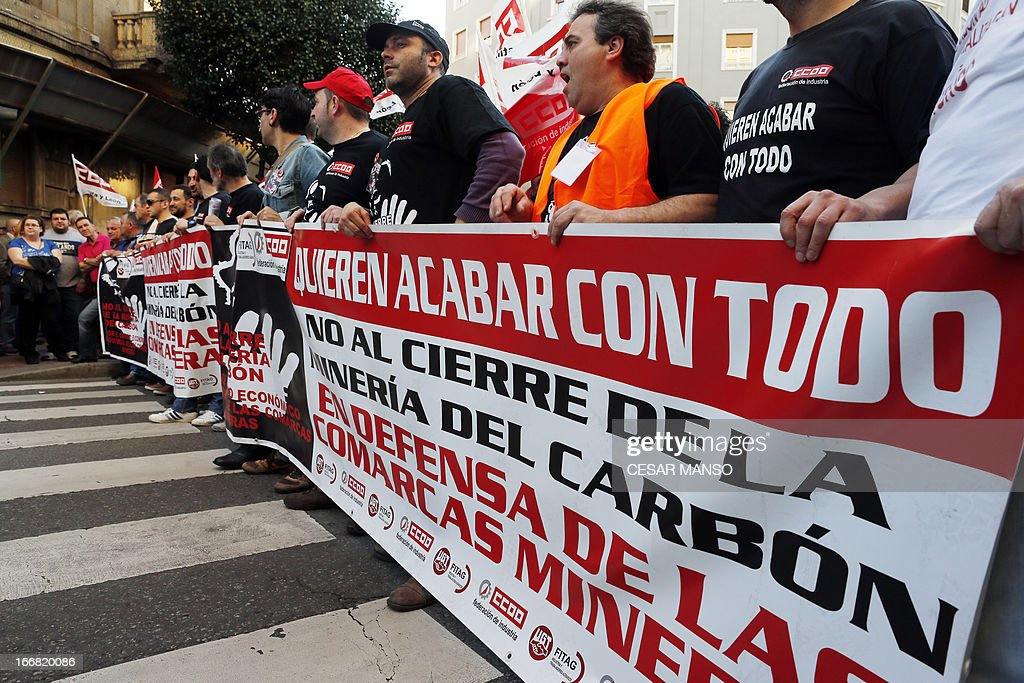 Spanish coal miners hold a banner as they demonstrate through the streets of the city of Leon, northern Spain, on April 17, 2013. The two most represented unions in mining, UGT and CCOO require the Spanish government to honour its commitments, responsibilities and obligations to the mining industry, as activating the aid to cover operating costs for companies and giving back jobs.