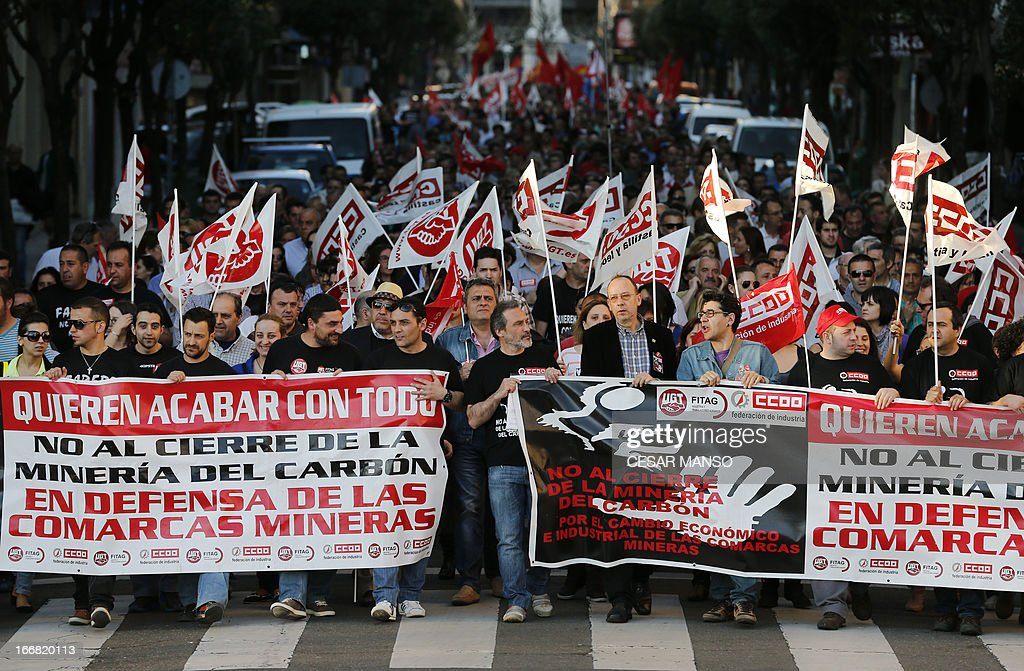Spanish coal miners hold banners as they demonstrate through the streets of the city of Leon, northern Spain, on April 17, 2013. The two most represented unions in mining, UGT and CCOO require the Spanish government to honour its commitments, responsibilities and obligations to the mining industry, as activating the aid to cover operating costs for companies and giving back jobs.