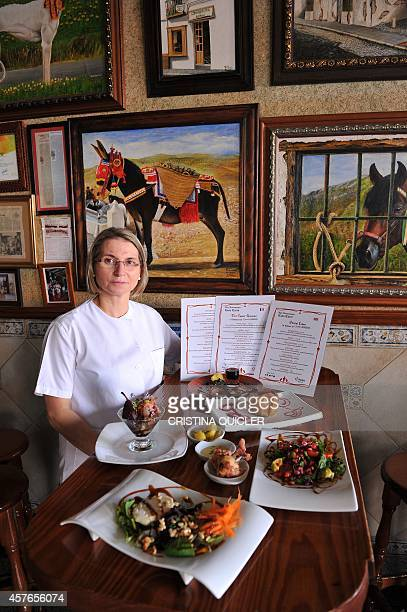 Spanish cook and restaurant owner Teresa Jimenez poses with the menu and dishes titled with the names of HBO TV serie 'Game of Thrones'' characters...
