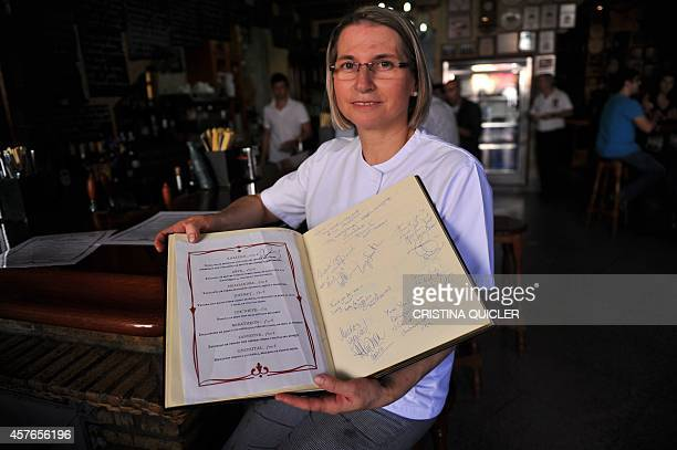 Spanish cook and restaurant owner Teresa Jimenez poses with the menu with dishes titled with the names of HBO TV serie 'Game of Thrones'' characters...