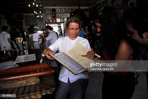 Spanish cook and restaurant owner Teresa Jimenez shows to a fan the menu with dishes titled with the names of HBO TV serie 'Game of Thrones''...