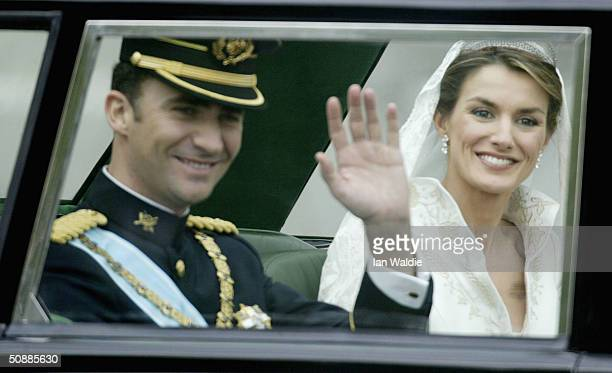 Spanish Crown Prince Felipe de Bourbon and his bride Letizia wave as they leave the Royal Palace May 22 2004 in Madrid