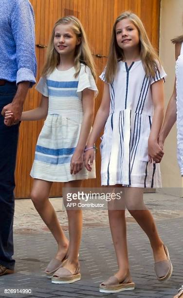 Spanish crown princess Leonor and princess Sofia walk down a street with their parents during the royal family's visit to the village of Soller on...