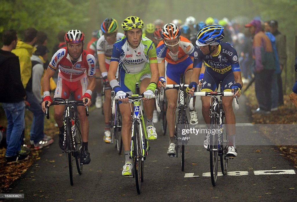 Spanish cyclist Joaquim Rodriguez (L) of Team Katusha, Italy's Vincenzo Nibali (C) and Spanish Alberto Contador (R) compete under heavy rain near Muro di Sormano on September 29, 2012, during the 106th Giro di Lombardia (Tour of Lombardy), a 251kms race from Bergamo to Lecco. Rodriguez won the race. AFP PHOTO / LUK BENIES