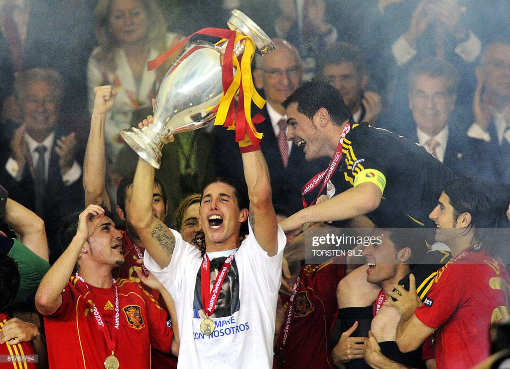 Spanish defender Sergio Ramos celebrates with the trophy and Spanish goalkeeper Iker Casillas (R) and other teammates after the Euro 2008 championships final football match Germany vs Spain on June 29, 2008 at Ernst-Happel stadium in Vienna, Austria. Spain won their first trophy in 44 years as they beat three-time champions Germany 1-0 in the Euro 2008 final. AFP PHOTO DDP / TORSTEN SILZ -- MOBILE SERVICES OUT --