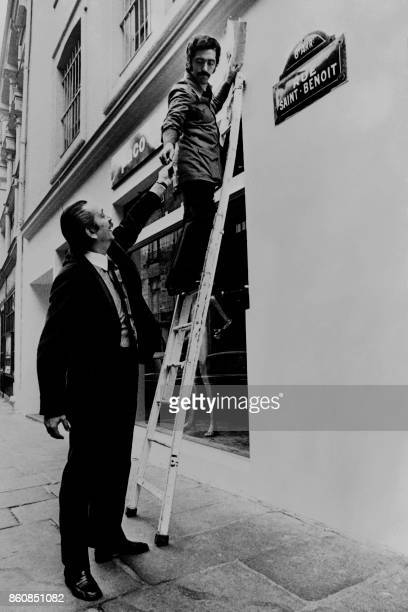 Spanish designer Paco Rabanne and Maurice Casanova fix the Business name above his new shop window on October 26 at the SaintBenoit street in the 6th...