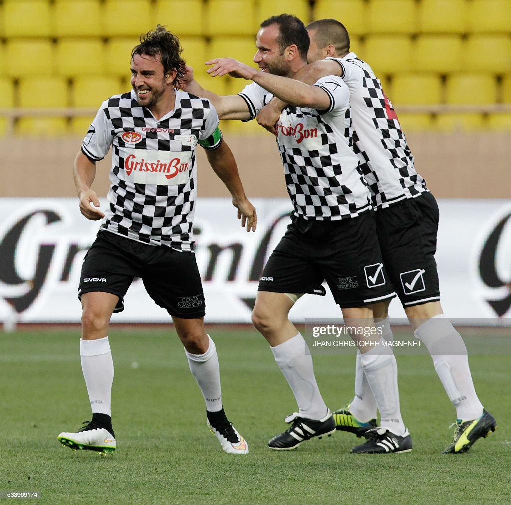 F1 Spanish driver Fernando Alonso (L) celebrates with teammates after scoring during a charity football match between Prince Albert's Star Team and the F1 'Nazionale Piloti' drivers' team, for the benefit of the 'Association Mondiale des Amis de l'Enfance' (Protection of Children Association) on May 24, 2016 at the Louis II Stadium, in Monaco. / AFP / JEAN