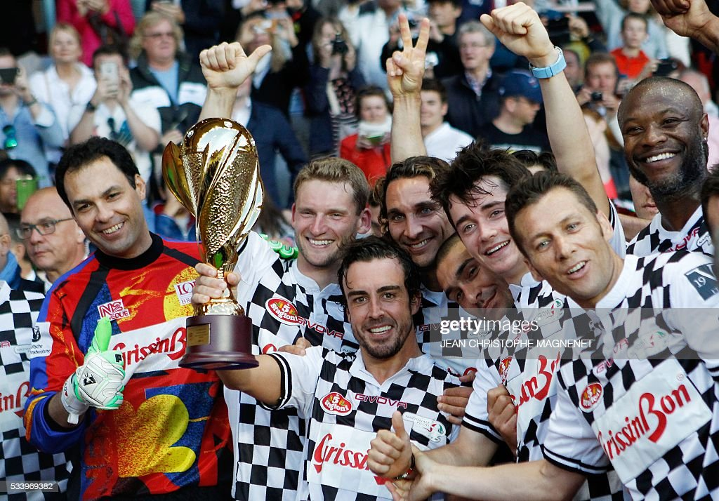 F1 Spanish driver Fernando Alonso (C) celebrates with teammates after a charity football match between Prince Albert's Star Team and the F1 'Nazionale Piloti' drivers' team, for the benefit of the 'Association Mondiale des Amis de l'Enfance' (Protection of Children Association) on May 24, 2016 at the Louis II Stadium, in Monaco. / AFP / JEAN