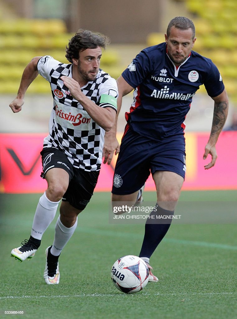 Spanish driver Fernando Alonso (L) controls the ball during a charity football match between Prince Albert's Star Team and the F1 'Nazionale Piloti' drivers' team, for the benefit of the 'Association Mondiale des Amis de l'Enfance' (Protection of Children Association) on May 24, 2016 at the Louis II Stadium, in Monaco. / AFP / JEAN