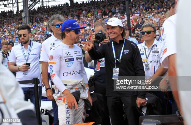 Spanish driver Fernando Alonso is greeted by former Brazilian driver Emerson Fittipaldi on the starting grid of the 101st Indy 500 on May 28 in...