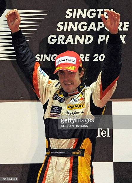Spanish driver Fernando Alonso of Renault celebrates as he walks onto the podium following his victory in the Singapore Grand Prix Formula One final...
