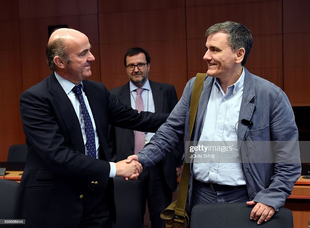Spanish Economy Minister Cristobal Montoro Romero (L) shakes hands with Greek Finance Minister Euclid Tsakalotos (R) during a Eurogroup meeting at the European Union headquarters in Brussels on May 24, 2016. Eurozone finance ministers said they hoped to unlock vital bailout cash for Greece on May 24, but warned of tough talks on debt relief that the IMF has demanded as the price for staying with the programme. / AFP / JOHN