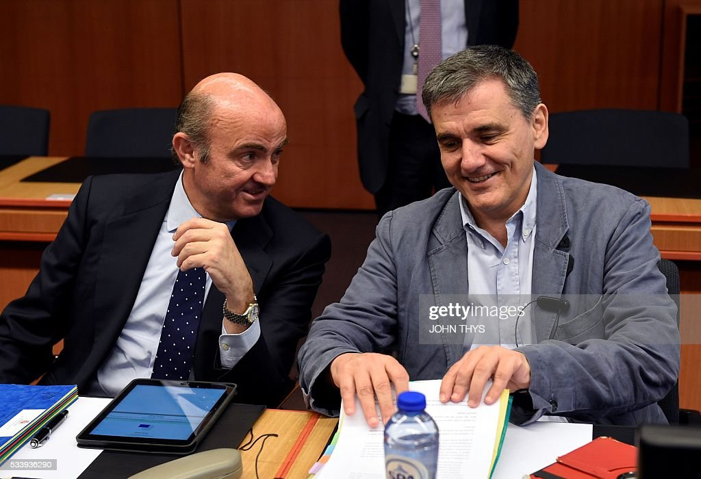 Spanish Economy Minister Cristobal Montoro Romero (L) talks with Greek Finance Minister Euclid Tsakalotos (R) during a Eurogroup meeting at the European Union headquarters in Brussels on May 24, 2016. Eurozone finance ministers said they hoped to unlock vital bailout cash for Greece on May 24, but warned of tough talks on debt relief that the IMF has demanded as the price for staying with the programme. / AFP / JOHN