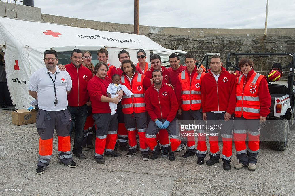 Spanish emergency services pose with a would-be immigrant baby rescued in the Strait of Gibraltar, on December 6, 2012. Spanish emergency services intercepted today four inflatable boats carrying sub-Saharan would-be immigrants accross the Strait of Gibraltar. AFP PHOTO/ MARCOS MORENO