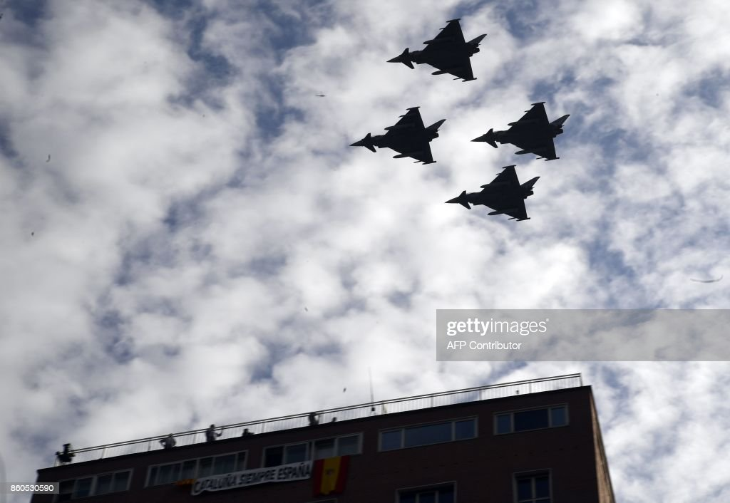 Spanish Eurofighter planes fly during the Spanish National Day military parade in Madrid on October 12, 2017. A Spanish Eurofighter jet crashed today after taking part in a military display in Madrid for Spain's national day, killing its pilot, the defence ministry said. Spain marks its national day today under high tension as the country reels from the biggest challenge to unity in a generation with its Catalan region threatening to break away. SORIANO